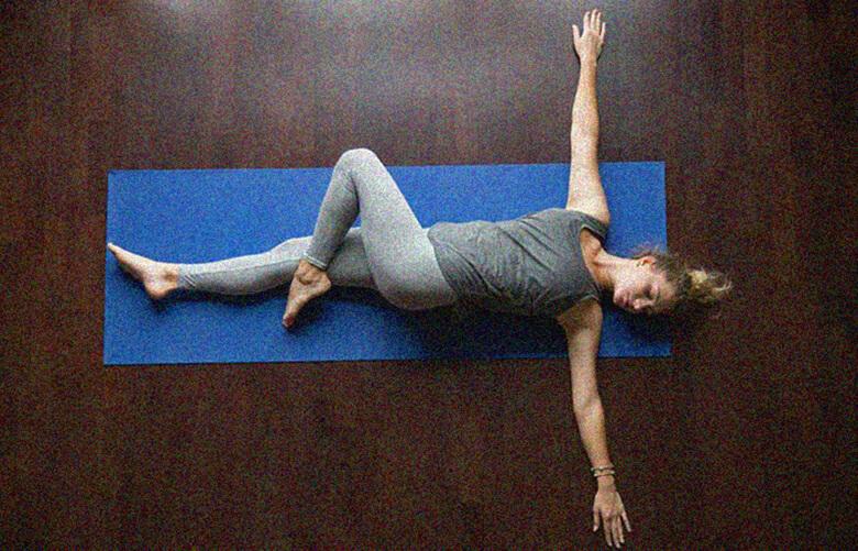 Положение лежащего треугольника с согнутой ногой йога